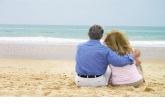 Couple sitting on the beach sand